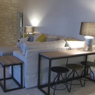 Foto di un soggiorno chic di medie dimensioni e chiuso con pareti bianche, pavimento in pietra calcarea, camino classico, cornice del camino in pietra, nessuna TV e pavimento beige