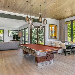Foto de salón abierto, minimalista, grande, con paredes blancas, suelo de madera clara, televisor en una esquina y suelo marrón