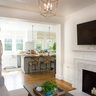 サンタバーバラの中サイズのビーチスタイルのおしゃれなLDK (無垢フローリング、茶色い床、白い壁、標準型暖炉、漆喰の暖炉まわり、壁掛け型テレビ) の写真