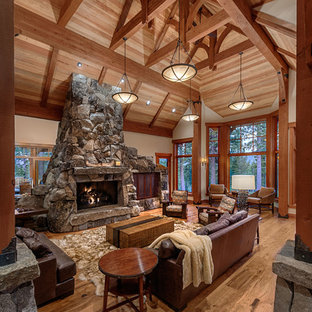 Large mountain style formal and open concept medium tone wood floor and brown floor living room photo in Sacramento with beige walls, a two-sided fireplace, a stone fireplace and no tv