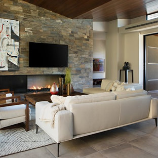 Large modern formal open plan living room in Phoenix with brown walls, limestone flooring, a ribbon fireplace, a stone fireplace surround, a wall mounted tv and beige floors.