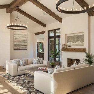 Bild på ett medelhavsstil allrum med öppen planlösning, med vita väggar, mellanmörkt trägolv, en bred öppen spis och brunt golv