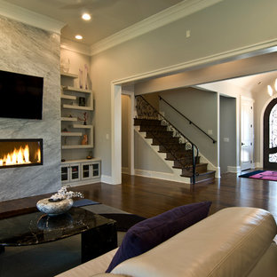 Mid-sized traditional enclosed living room in Charlotte with beige walls, dark hardwood floors, a ribbon fireplace, a stone fireplace surround and a wall-mounted tv.