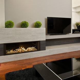 Imagen de salón abierto, moderno, grande, con paredes grises, suelo de madera oscura, chimenea lineal, marco de chimenea de baldosas y/o azulejos y televisor colgado en la pared