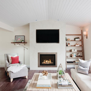 Design ideas for a traditional living room in Denver with white walls, a standard fireplace, a wall mounted tv and brown floors.