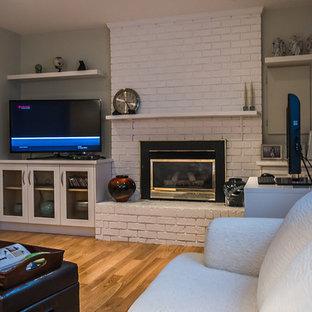 バンクーバーの中くらいのトラディショナルスタイルのおしゃれな独立型リビング (グレーの壁、淡色無垢フローリング、吊り下げ式暖炉、レンガの暖炉まわり、据え置き型テレビ、茶色い床) の写真