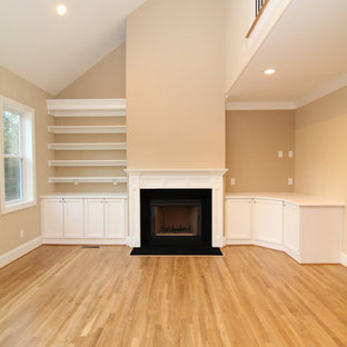 ローリーの中サイズのトランジショナルスタイルのおしゃれなリビングロフト (ベージュの壁、無垢フローリング、標準型暖炉、木材の暖炉まわり、埋込式メディアウォール) の写真
