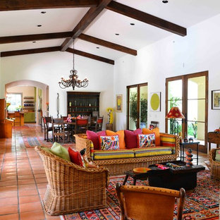 Large formal open plan living room in Houston with white walls, terracotta flooring, a standard fireplace, a tiled fireplace surround, no tv and red floors.