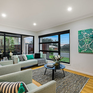 Design ideas for a contemporary open concept living room in Brisbane with white walls, medium hardwood floors, no fireplace and a freestanding tv.