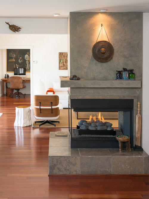 living room idea in los angeles with a two sided fireplace