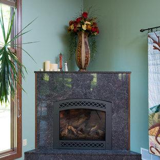 Immagine di un grande soggiorno american style aperto con pareti verdi, pavimento in legno massello medio, camino ad angolo, cornice del camino in intonaco e TV autoportante