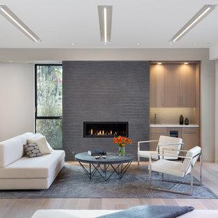 Idéer för att renovera ett funkis allrum med öppen planlösning, med beige väggar, ljust trägolv, en bred öppen spis, en spiselkrans i trä och beiget golv