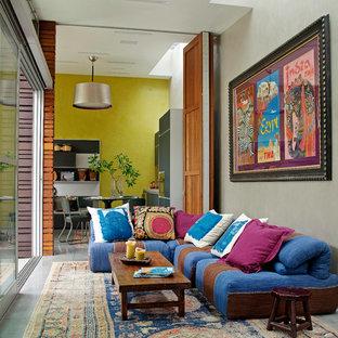 Immagine di un soggiorno bohémian di medie dimensioni e aperto con pavimento in cemento, sala formale, pareti grigie, nessun camino e nessuna TV