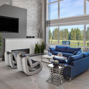 エドモントンの広いコンテンポラリースタイルのおしゃれなリビングロフト (グレーの壁、セラミックタイルの床、標準型暖炉、タイルの暖炉まわり、埋込式メディアウォール、グレーの床) の写真