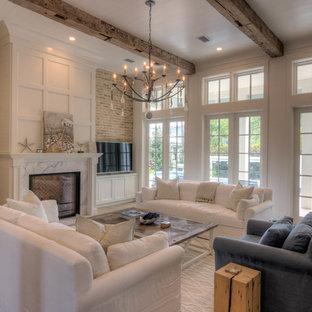 アトランタの大きいビーチスタイルのおしゃれなLDK (白い壁、淡色無垢フローリング、標準型暖炉、石材の暖炉まわり、壁掛け型テレビ、ベージュの床) の写真