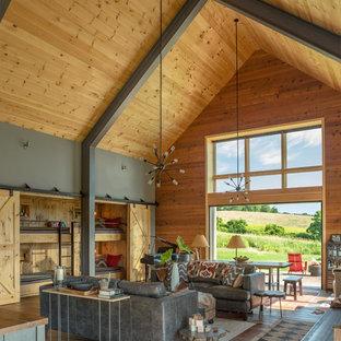 Cette photo montre un grand salon moderne ouvert avec une salle de réception, un mur marron, un sol en bois brun, aucun téléviseur et un sol marron.