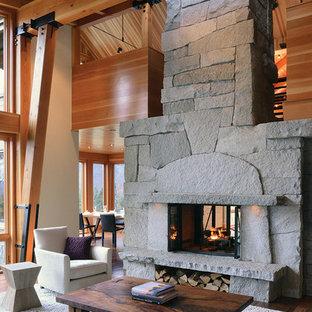 他の地域の中サイズのラスティックスタイルのおしゃれなLDK (フォーマル、両方向型暖炉、石材の暖炉まわり、マルチカラーの壁、無垢フローリング、テレビなし) の写真