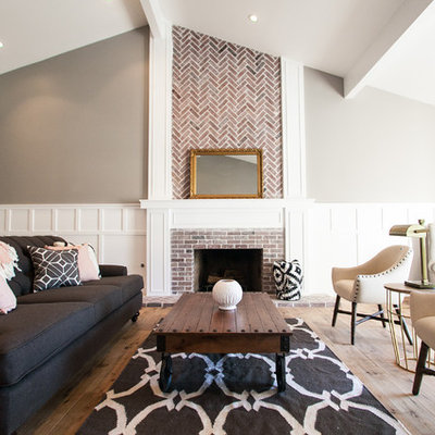 Mid-sized cottage open concept medium tone wood floor living room photo in Phoenix with gray walls, a standard fireplace and a brick fireplace