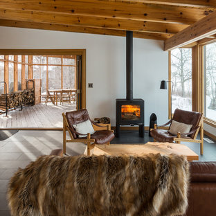 Design ideas for a small country enclosed living room in Other with white walls, ceramic floors, a wood stove, a metal fireplace surround and grey floor.