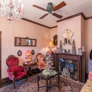 オースティンの大きいヴィクトリアン調のおしゃれな独立型リビング (フォーマル、ピンクの壁、濃色無垢フローリング、標準型暖炉、石材の暖炉まわり、テレビなし、茶色い床) の写真