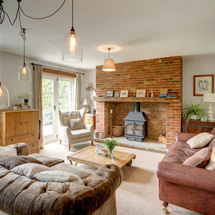 Farmhouse enclosed carpeted and beige floor living room photo in Kent with a brick fireplace, a tv stand, white walls and a wood stove