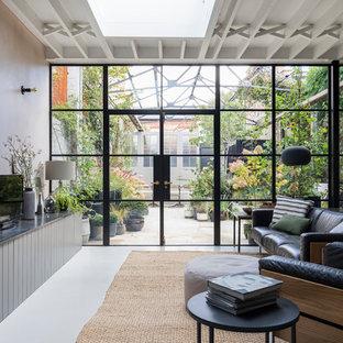 Imagen de salón abierto, urbano, con paredes rosas, suelo de cemento, pared multimedia y suelo gris