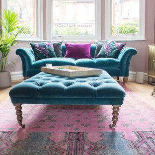 Foto di un soggiorno bohémian di medie dimensioni e chiuso con angolo bar, pareti rosa, pavimento in laminato, camino classico, cornice del camino in pietra e TV a parete