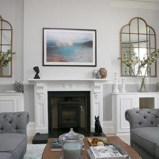 Diseño de salón abierto, clásico renovado, grande, con paredes grises, moqueta, estufa de leña y marco de chimenea de piedra