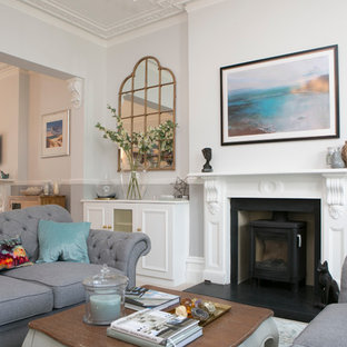 This is an example of a large classic formal open plan living room in Dorset with grey walls, carpet, a wood burning stove, a stone fireplace surround and no tv.