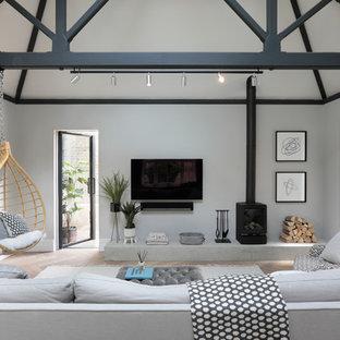 Ejemplo de salón tradicional renovado con paredes grises, suelo de madera clara, estufa de leña, marco de chimenea de metal, televisor colgado en la pared y suelo beige
