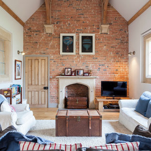 Farmhouse enclosed living room in London with white walls, a standard fireplace, a freestanding tv and light hardwood flooring.