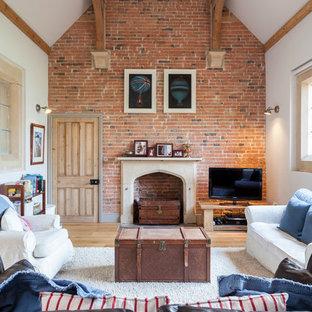 Modelo de salón cerrado, de estilo de casa de campo, con paredes blancas, chimenea tradicional, televisor independiente y suelo de madera clara