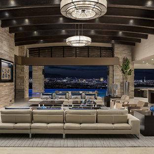 ラスベガスのサンタフェスタイルのおしゃれなLDK (横長型暖炉、壁掛け型テレビ、グレーの床) の写真