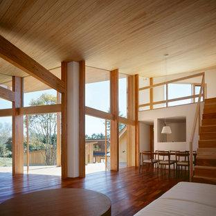 Modelo de salón abierto, moderno, de tamaño medio, con paredes blancas, suelo de madera oscura y suelo rojo