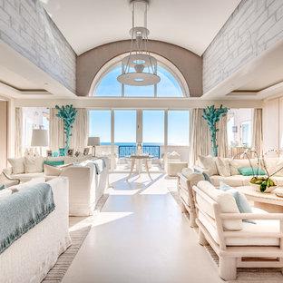 マイアミの巨大なビーチスタイルのおしゃれな独立型リビング (白い壁、コンクリートの床、標準型暖炉、石材の暖炉まわり、内蔵型テレビ、白い床) の写真
