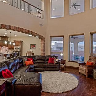 Foto de salón abierto, mediterráneo, grande, con paredes beige, suelo de madera en tonos medios, chimenea de esquina, marco de chimenea de piedra y televisor independiente