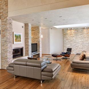 Idee per un soggiorno minimal con pareti beige, pavimento in legno massello medio, camino classico, TV autoportante e pavimento marrone