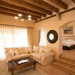 Immagine di un soggiorno country di medie dimensioni e aperto con sala formale, pareti beige, pavimento in terracotta e nessun camino