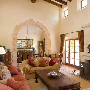 Immagine di un soggiorno country di medie dimensioni e chiuso con pareti beige, camino classico, cornice del camino in pietra, nessuna TV e sala formale