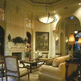 マイアミの大きい地中海スタイルのおしゃれなLDK (フォーマル、ベージュの壁、標準型暖炉、漆喰の暖炉まわり、テレビなし、磁器タイルの床、白い床) の写真
