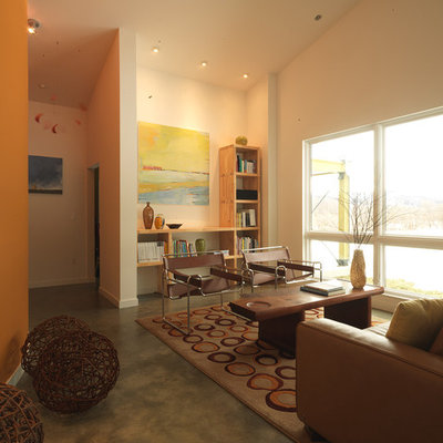 Example of a large farmhouse enclosed concrete floor living room library design in Burlington with orange walls