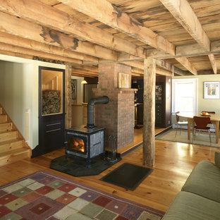 Immagine di un soggiorno country di medie dimensioni e aperto con pareti beige, stufa a legna, pavimento in legno massello medio e parete attrezzata