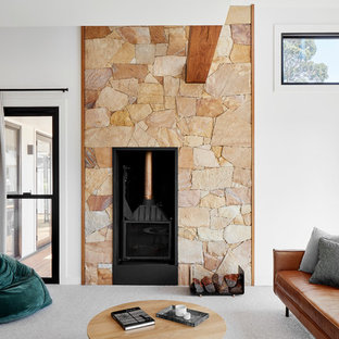 This is an example of a mid-sized country open concept living room in Melbourne with white walls, carpet, a wood stove, no tv, grey floor and a stone fireplace surround.