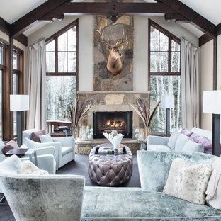 Idée de décoration pour un grand salon chalet ouvert avec un mur beige, une cheminée standard, un manteau de cheminée en pierre, une salle de réception, un sol en bois foncé, aucun téléviseur et un sol marron.