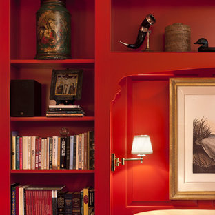 This is an example of a mid-sized traditional open concept living room in Philadelphia with a library, red walls, carpet, a standard fireplace, a metal fireplace surround and no tv.