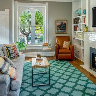 Mittelgroßes, Offenes Modernes Wohnzimmer mit grauer Wandfarbe, dunklem Holzboden, Kamin, gefliester Kaminumrandung, Wand-TV und braunem Boden in Denver