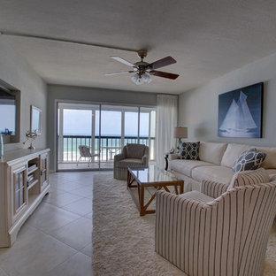 Ejemplo de salón abierto, costero, pequeño, sin chimenea, con paredes grises, televisor colgado en la pared y suelo de mármol