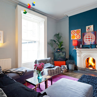 Living room - mid-sized eclectic enclosed dark wood floor and brown floor living room idea in Dublin with multicolored walls, a standard fireplace, a metal fireplace and a tv stand