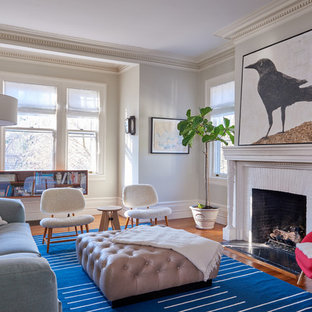 Inspiration for a transitional medium tone wood floor and brown floor living room remodel in New York with gray walls, a standard fireplace and a brick fireplace