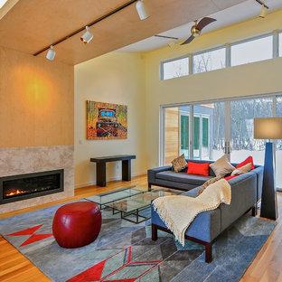 Diseño de salón actual con paredes amarillas, suelo de madera en tonos medios y chimenea lineal